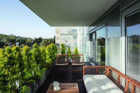 מרפסת הדירה רוצפה בדק עץ ורוהטה בכורסאות קלועות בהשראת תאילנד. צילום: עמית גרון