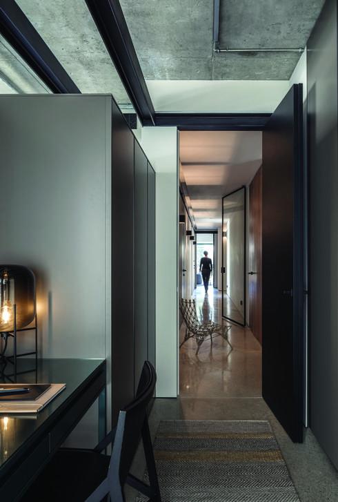 מבט מאגף השינה לעבר המסדרון, המופרד במחיצת זכוכית שקופה ממוסגרת פלדה. צילום: עמית גרון